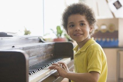 Mixed race boy playing the piano